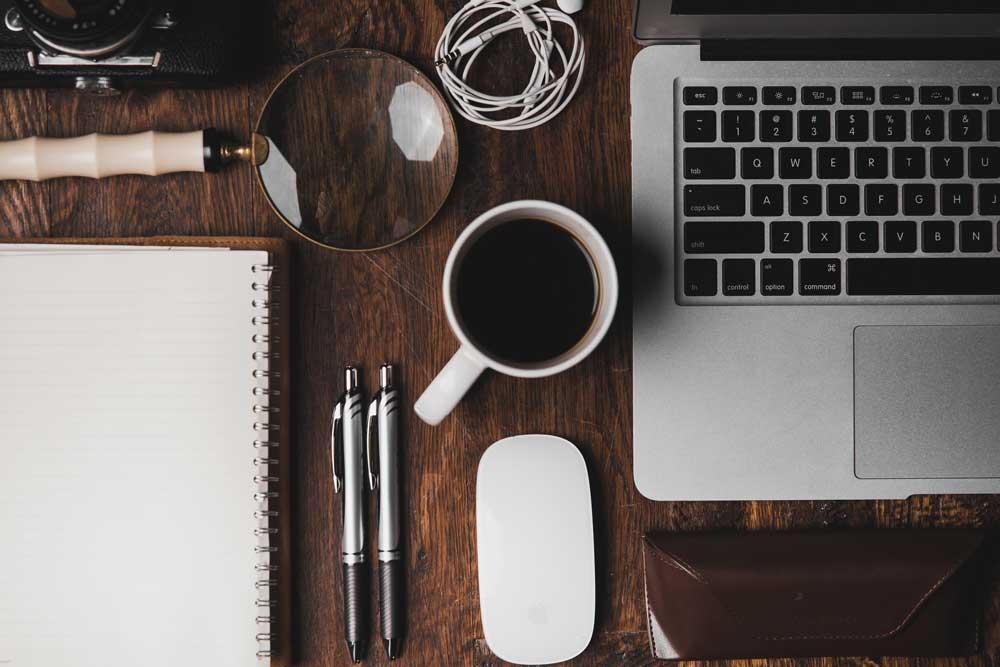 Caderno, canetas, caneca de café, fone de ouvido, mouse e notebook em cima de mesa de madeira