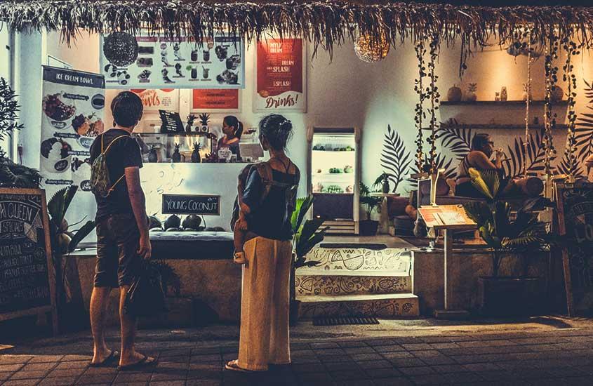 Viajantes observam placas com preços de comidas, importante para quem quer viver em Bali