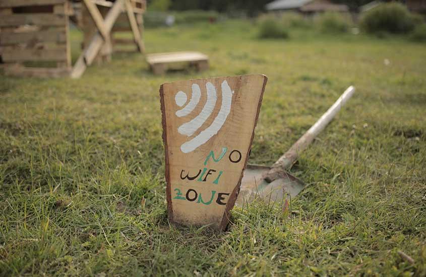 Placa de madeira em grama onde há escrito ''no wi-fi zone''