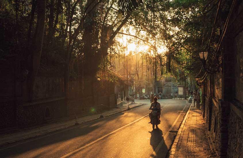 Viajante circula de moto em uma estrada, um bom transporte para quem quer viver em Bali