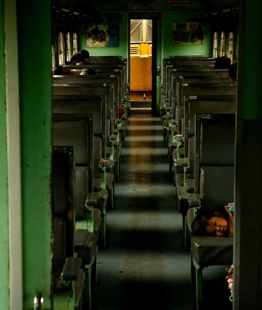 criança deitada em banco de trem em Bangkok