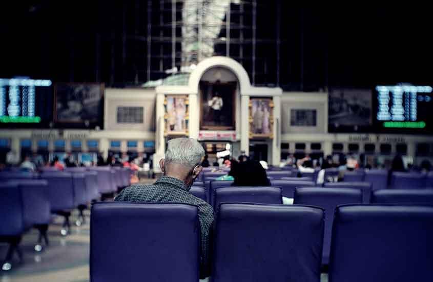 homem sentado em cadeira azul em estação em Bangkok