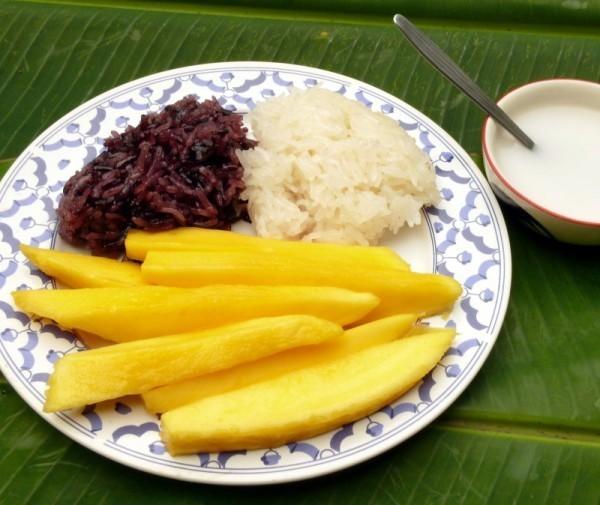 Prato branco e azul, com arroz e mangas, um prato da culinária tailandesa conhecido como khao nia mamuang