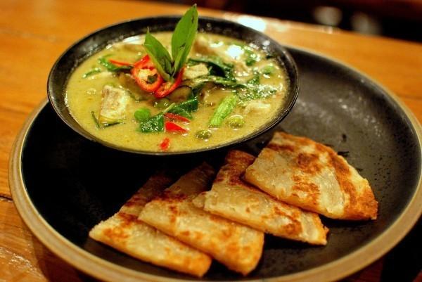 Kaeng Khiao wan um curry verde doce da culinária tailandesa, servido em tigela preta, em cima de mesa de madeira