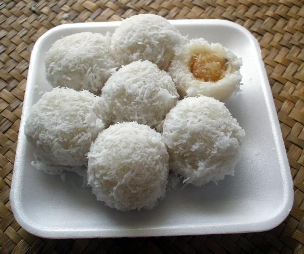 bolinhas de Khanom tom, uma mistura de farinha de arroz glutinoso e água, enroladas em coco ralado, em cima de vasilha e isopor