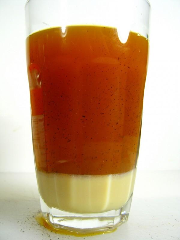 Copo de vidro com leite e chá misturado com flor de laranjeira, em cima de mesa branca