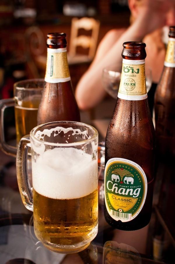 Caneca de vidro com cerveja ao lado de garrafa de vidro marrom de Chang, a cerveja mais vendida da Tailândia