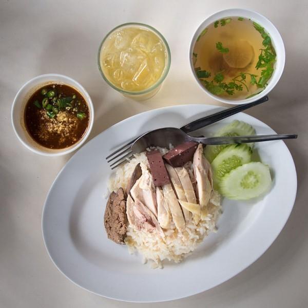 Arroz com frango e pepino em prato branco, onde há em cima uma colher e um garfo, em uma mesa branca
