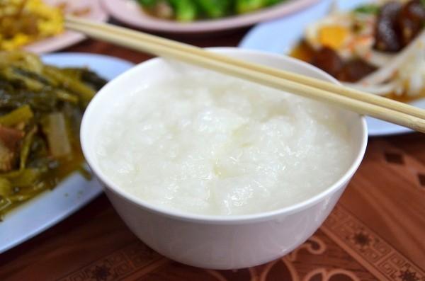Arroz com frango e pepino em prato branco, da culinária tailandesa, onde há em cima uma colher e um garfo, em uma mesa branca