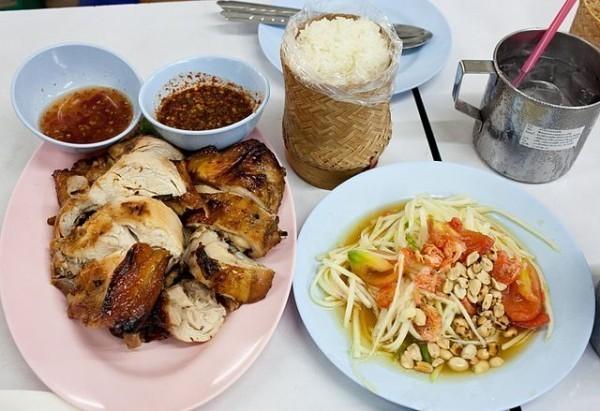 Mesa branca onde há um prato rosa com frango e um prato branco com salada de mamão, comum na culinária tailandesa