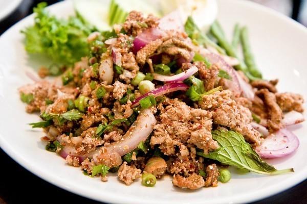 Laap pet uma comida típica da culinária tailandesa feito com pato, picado, servida em prato branco