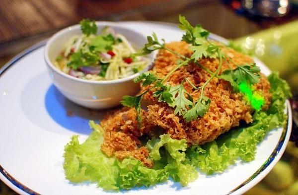 Yam pla duk fu uma comida típica da culinária tailandesa feita com peixe crocante, servida em prato branco com salada de manga