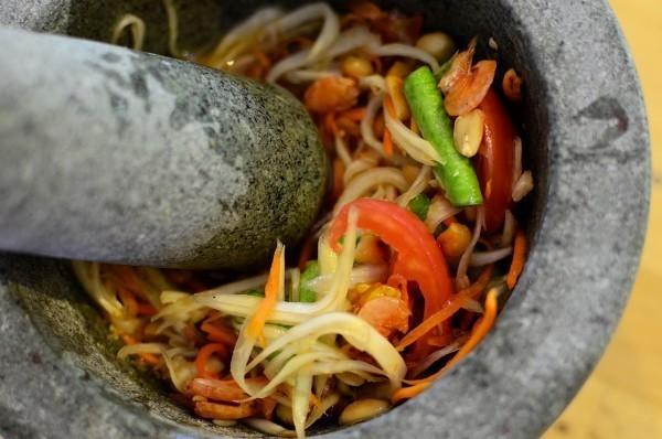 Pilão misturando salada com limão, pimentão, sal, molho de peixe, e açúcar dentro de vasilha