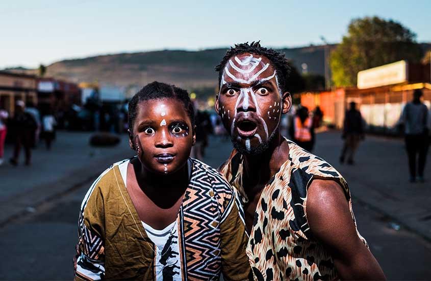 dois sul-africanos com rosto pintado com tinta branca, fazem pose de espanto para foto em rua de Joanesburgo áfrica do sul, durante o dia