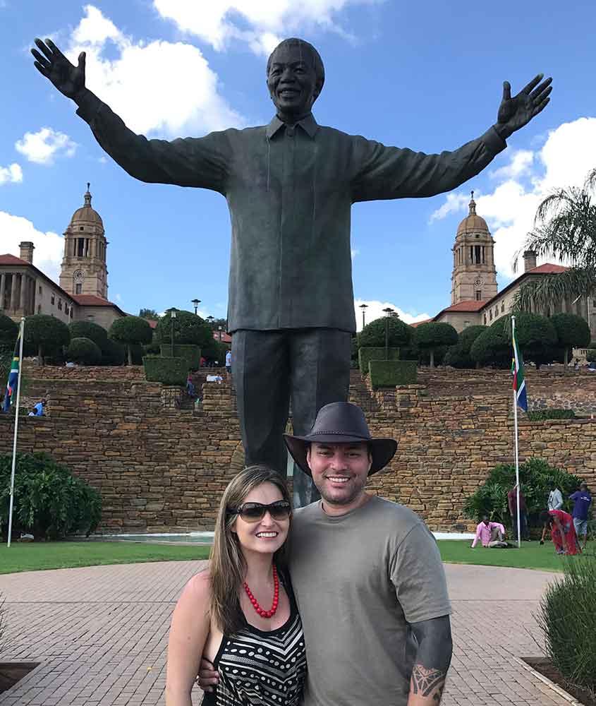 viajantes sorriem em frente a estátua de Nelson Mandela em Pretória, capital administrativa da África do Sul