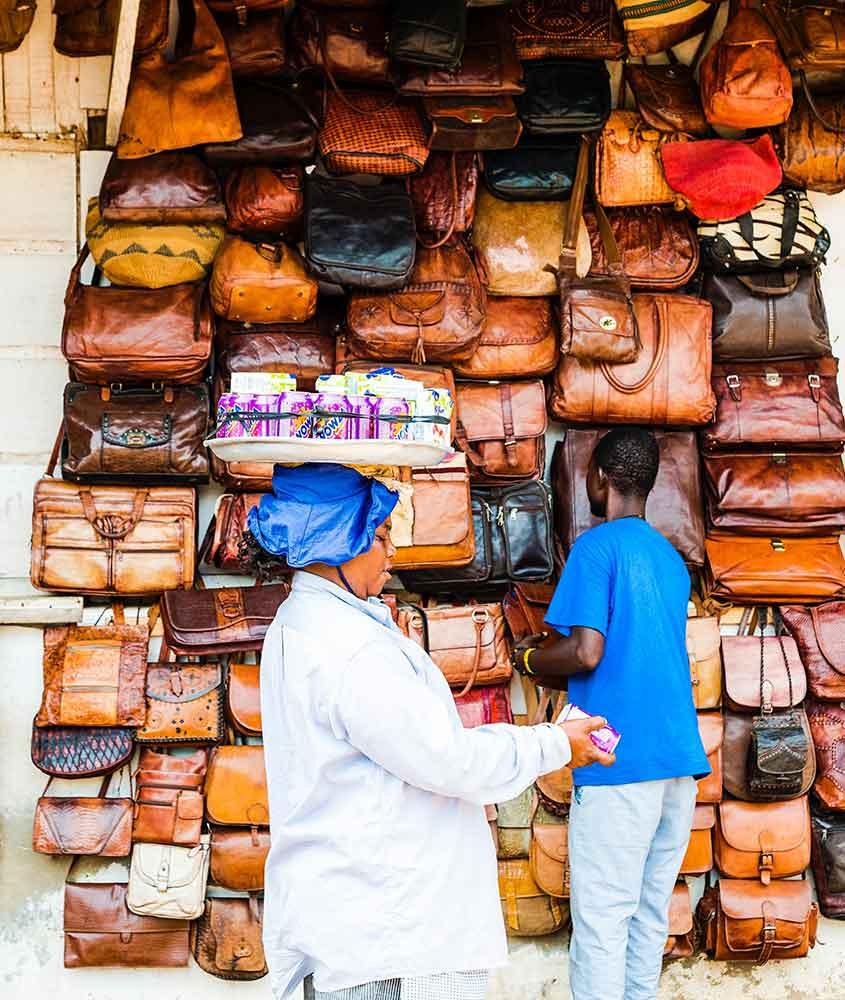 homem observa bolsas marrons expostas para venda em Mercado Neighbourgoods