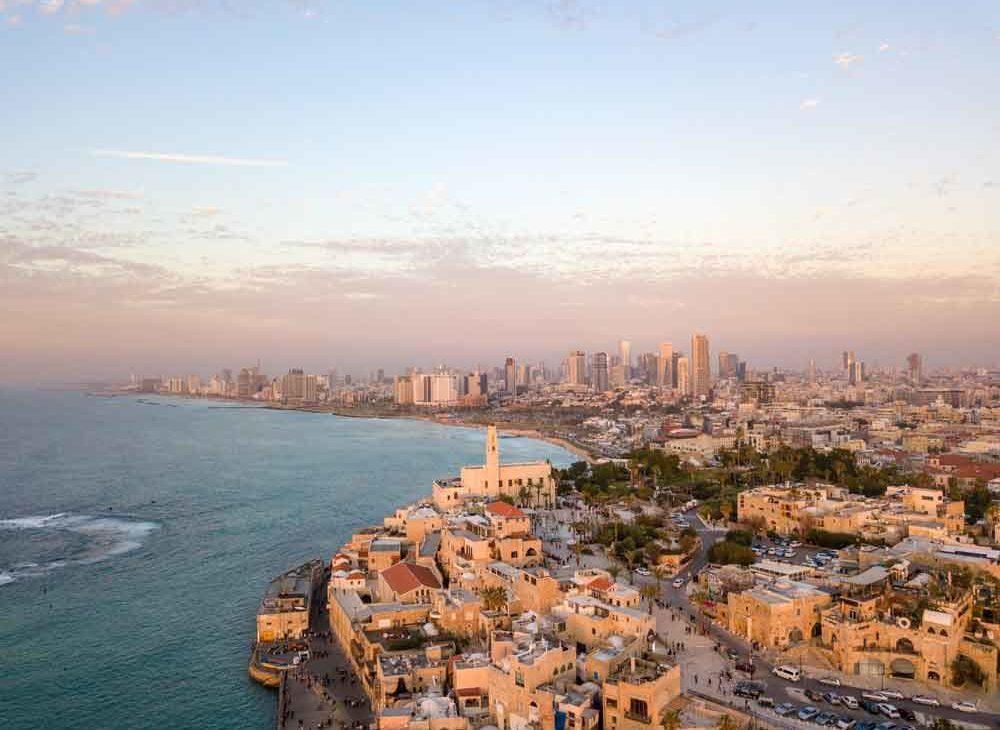 Vista área, durante o dia, de mar, construções como museus, casas e prédios e, carros e pessoas, em Tel Aviv-Yafo, cidade de Israel.