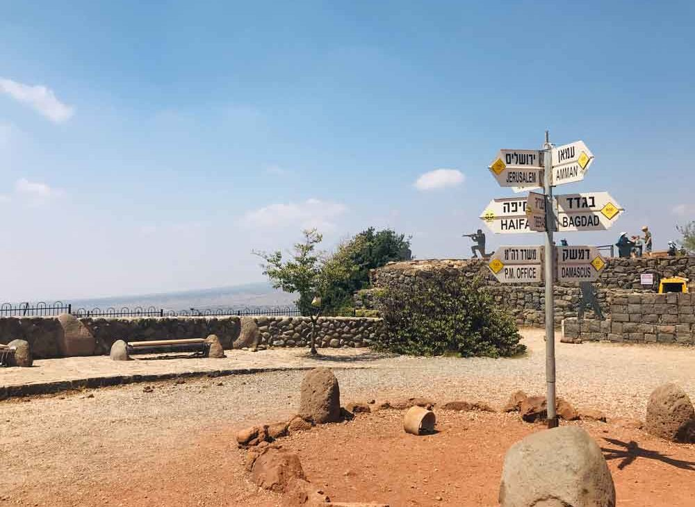Rua em Colinas de Golã, durante o dia, onde há um poste com placas, sinalizando direção de lugares como Jerusalém, e Haifa, cidades de Israel.