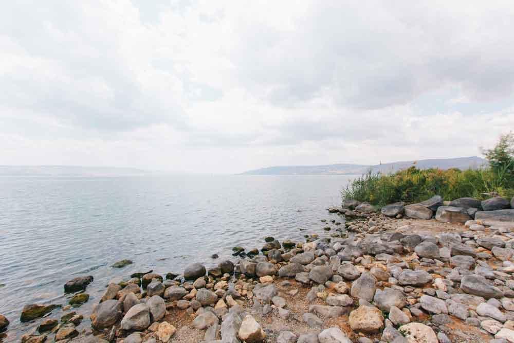 Pedras às margens das águas do Mar da Galileia, durante ao dia, um dos lugares mais visitados por turistas durante uma viagem para Israel.