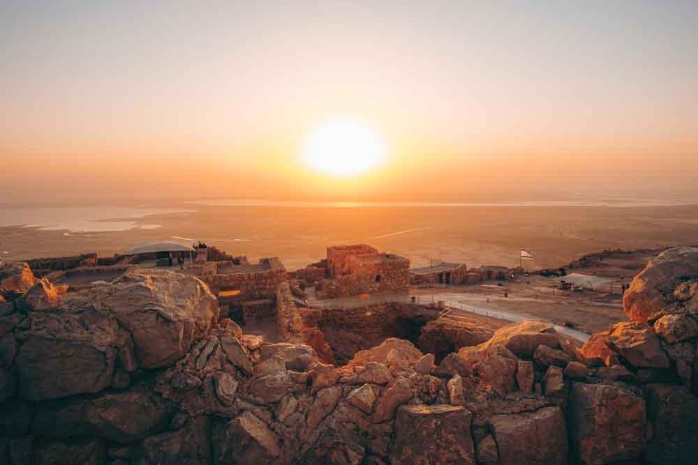 Vista área, ao amanhecer, de Masada, uma fortaleza natural com penhascos íngremes e terreno acidentado e, uma das melhores atrações para se conhecer durante uma viagem para Israel.