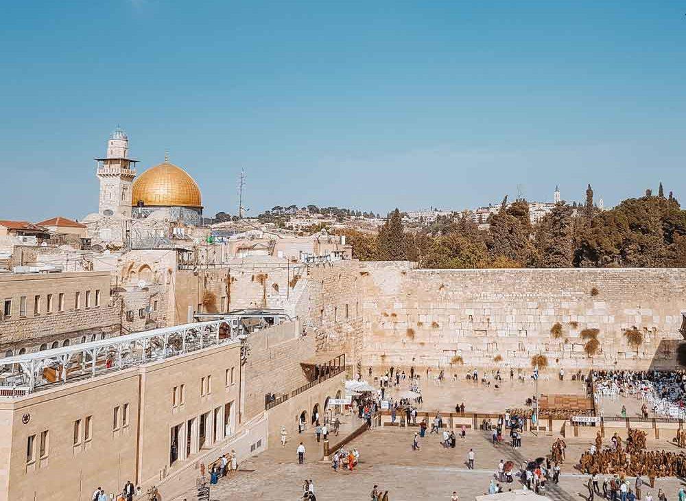 Pessoas andando em frente a uma antiga construção em Jerusalém, uma das cidades mais visitadas por turistas em viagem para Israel