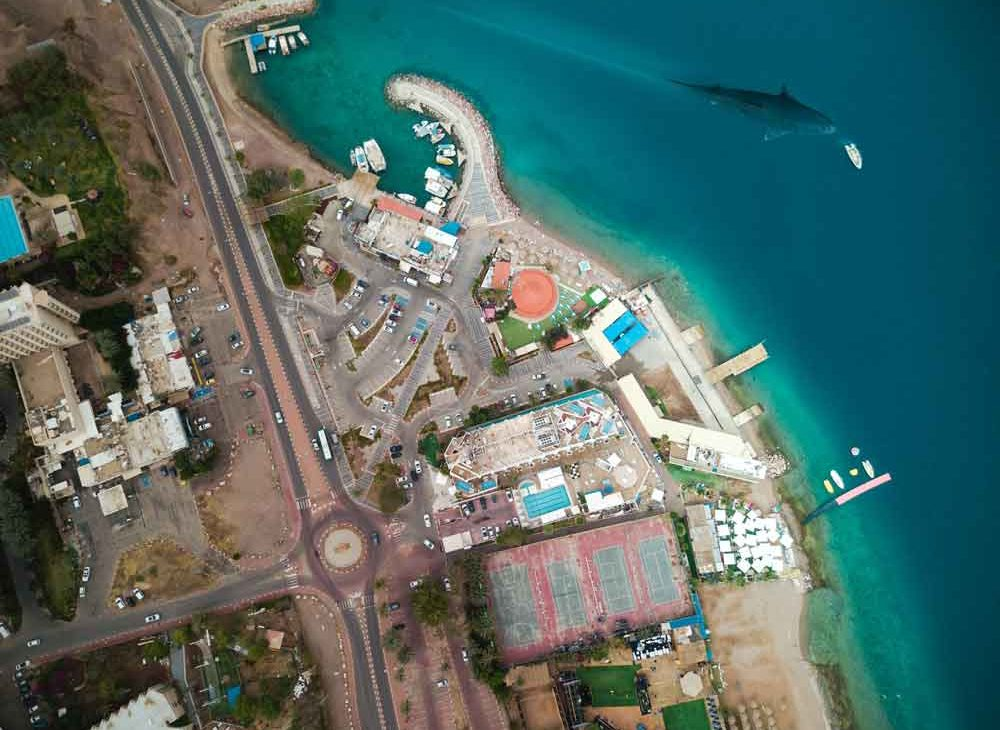 Vista aérea do mar azul, prédios, quadras e estradas de Eilat, cidade turísticas ideal para quem quer fazer snorkelling e mergulho, durante uma viagem para Israel.