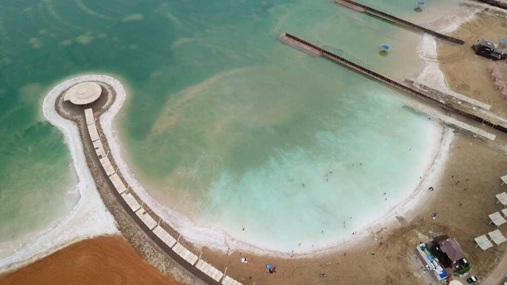 Vista aérea de Mar morto, lago em Israel, e areia ao seu redor, durante o dia.