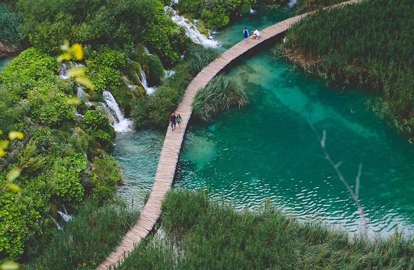 viajantes caminham em ponte sobre águas cristalinas de rio na Croácia