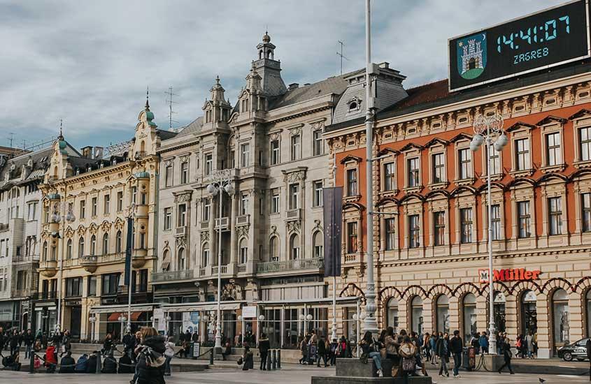 turistas caminham em frente a construções antigas em Zagreb, um lugar para incluir no roteiro na Croácia