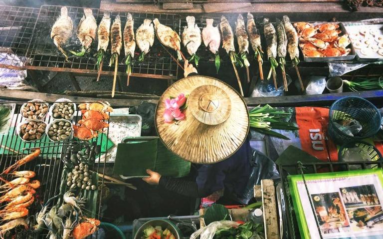 Mulher espeta um peixe ao lado de outros peixes expostos para venda em barraca de rua ambulante em Bangkok
