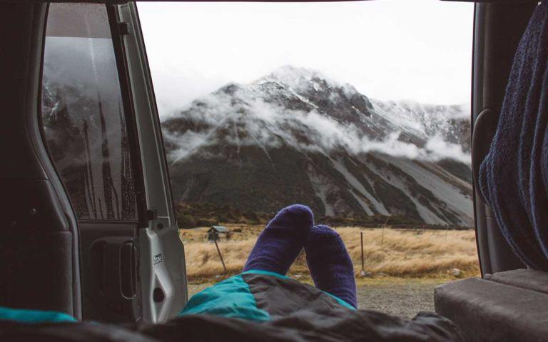 pés com meias, de viajante deitado em motorhome
