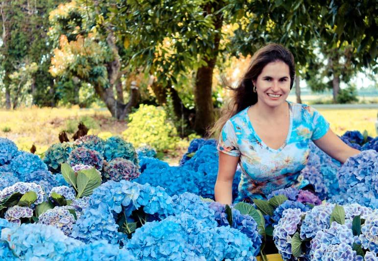 mulher sorri em campo de flores na nova zelândia