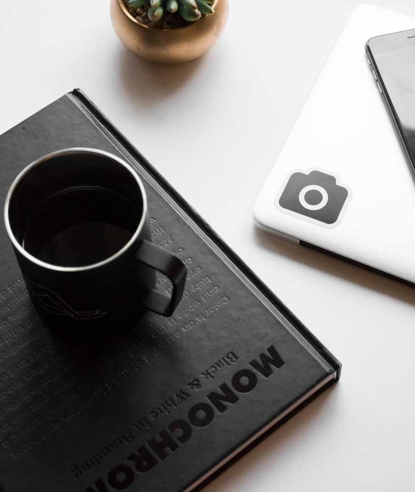 Caderno, notebook e caneca em cima de mesa câmera fotográfica e notebook em cima de mesa preta