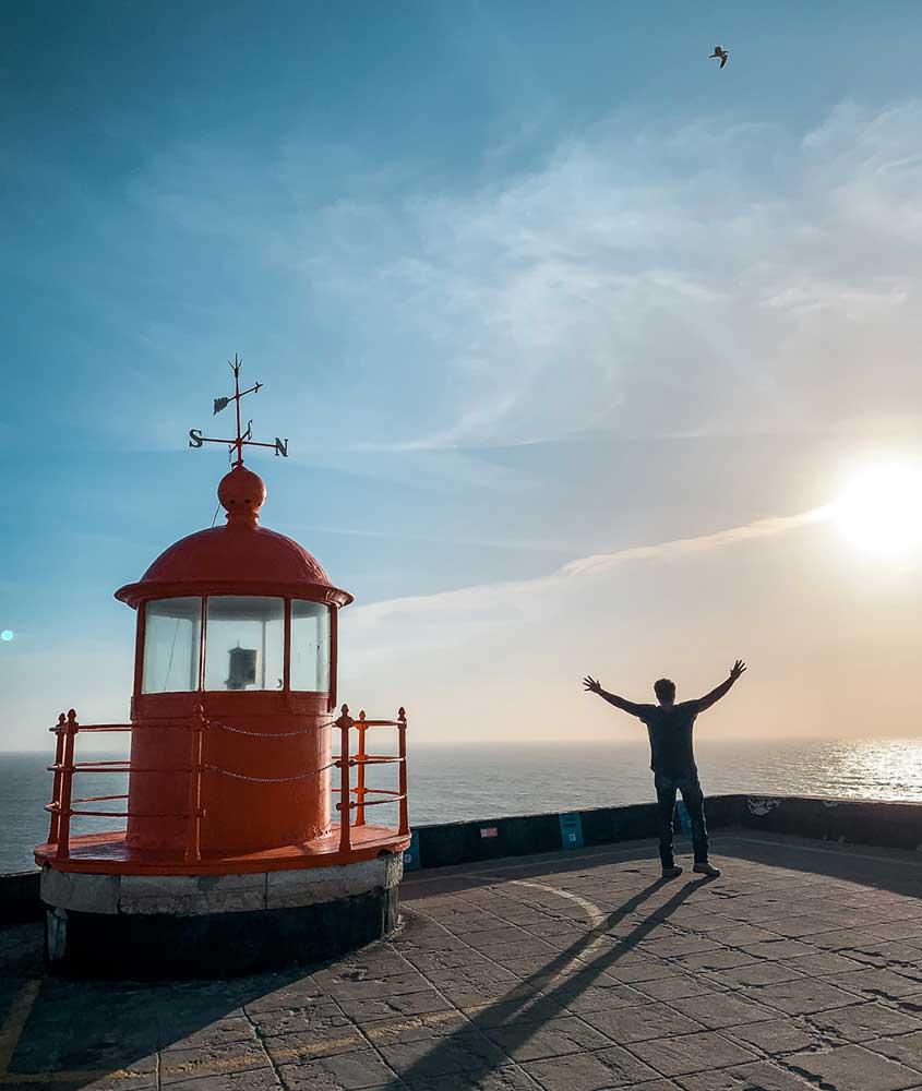 viajante de braços abertos em mirante, observa o mar