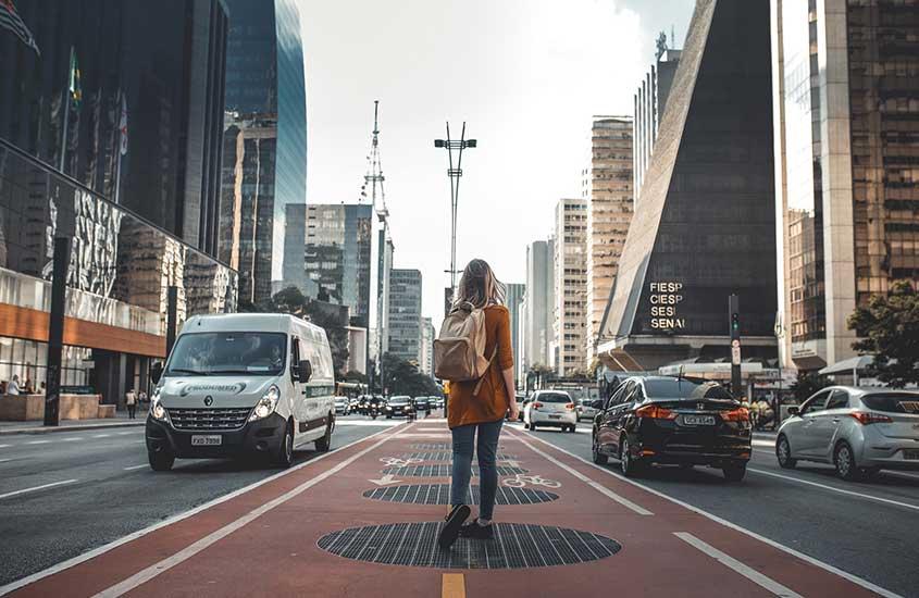 Nômade digital com mochila nas costas, caminha em rua, durante o dia