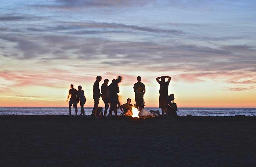 povo da nova Zelândia reunido em praia durante entardecer, uma atividade legal a se fazer ao morar na nova Zelândia