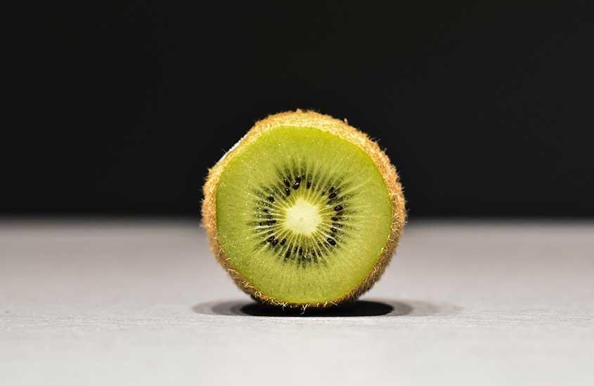 Kiwi cortado ao meio em cima de mesa branca