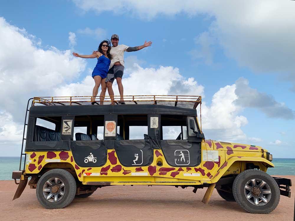 Bárbara Rocha e Vagner Alcantelado sorriem em cima de Jeep 4x4 amarelo, uma opção para quem busca o que fazer em Pipa