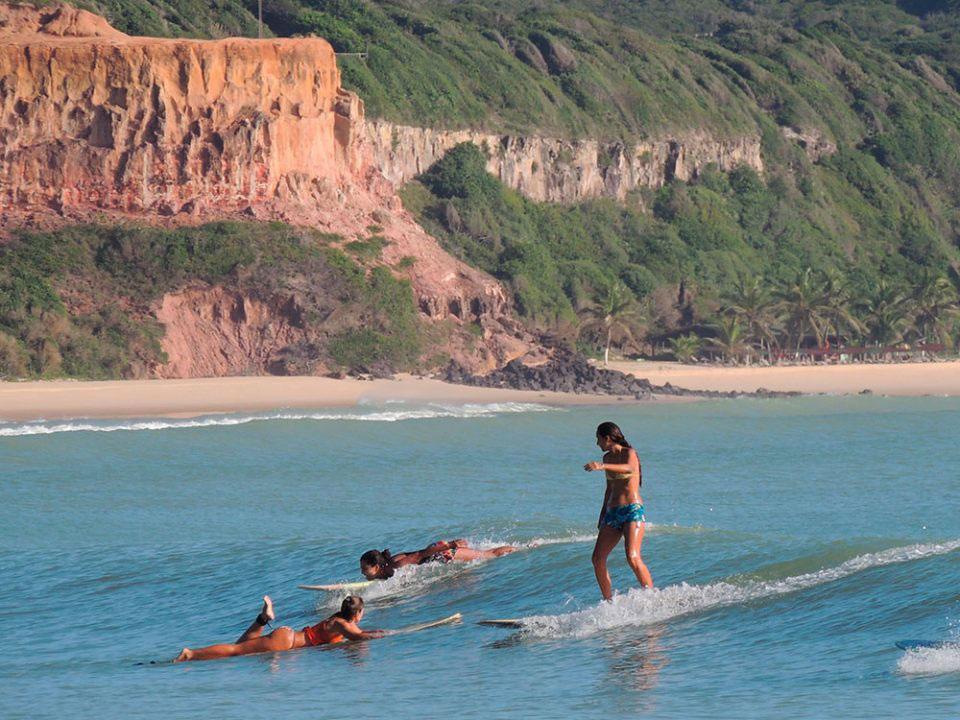 mulheres surfam em Praia do Madeiro em Pipa, uma opção para quem busca o que fazer em Pipa