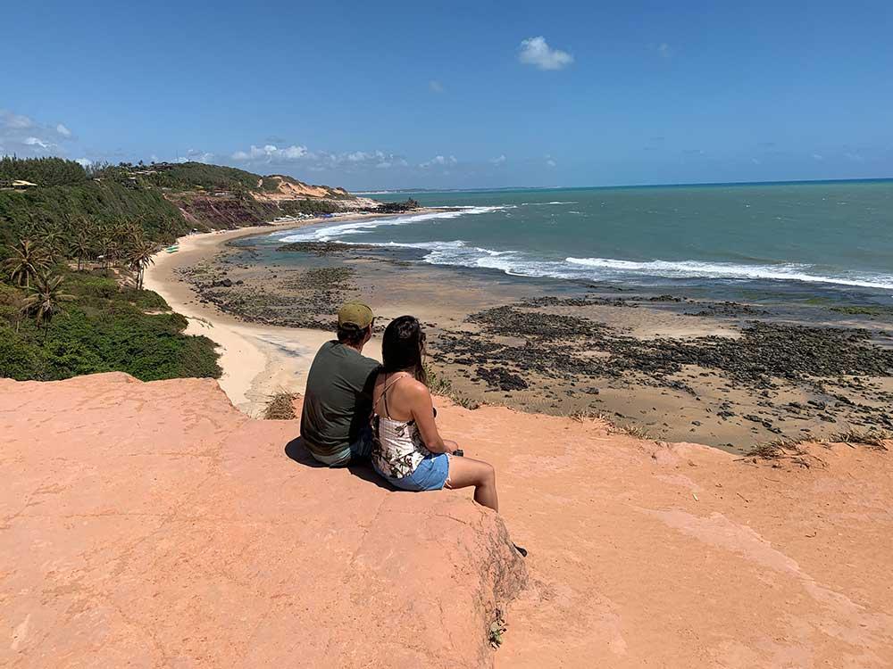 Casal sentado em falésias, durante o dia, obversa mar em Praia da Pipa, um dos lugares para viajar barato