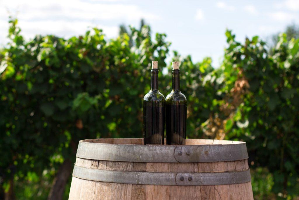 Garrafas de vinho em cima de barril