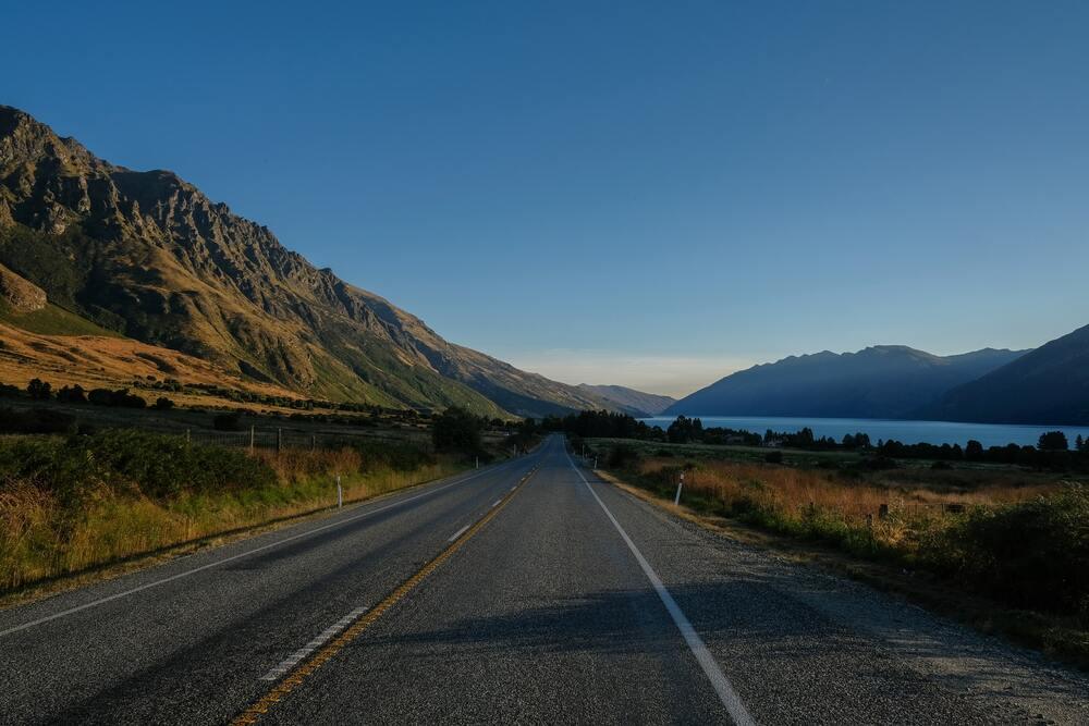 Estrada em Nova Zelândia. Mais uma das curiosidades da Nova Zelândia: há longas estradas, mas nenhuma parte do país fica tão longe do mar