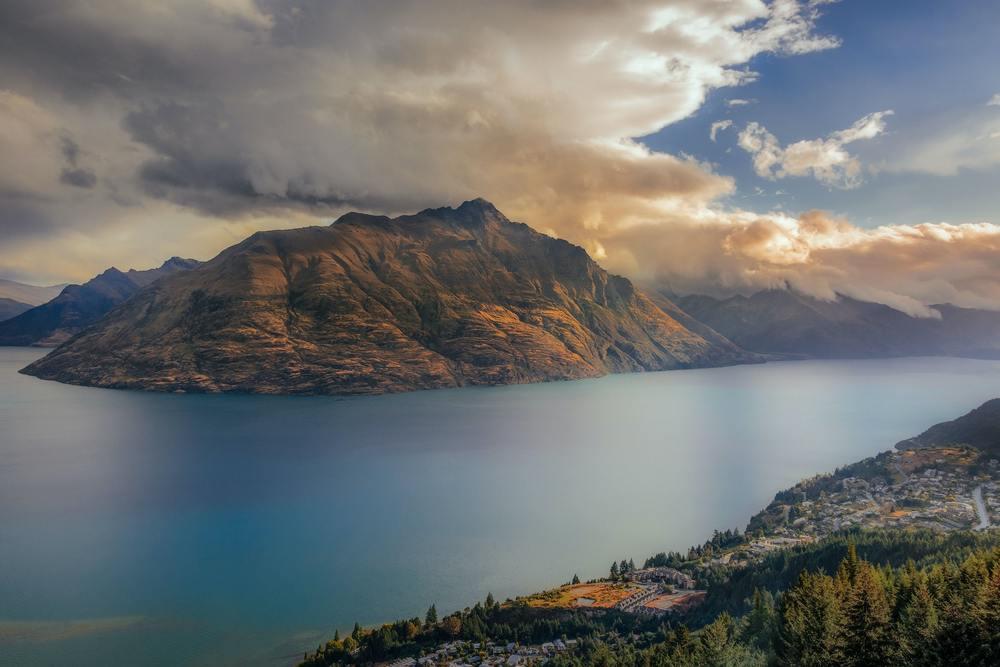 Vista aérea de montanhas, mar e céu da Nova Zelândia