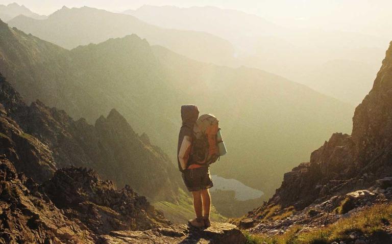 Viajante carrega mochila nas costas e observa em cima de uma pedra, montanhas, durante o dia