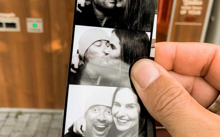 Pessoa segura foto revelada de casal se beijando e sorrindo em viagem a dois