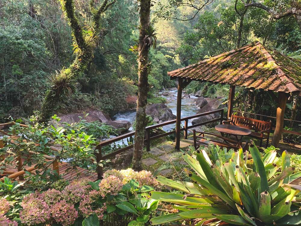 Bancos de madeira em jardim de pousada, em frente a cachoeira, em meio a árvores em Visconde de Mauá, um dos melhores lugares para viajar a dois