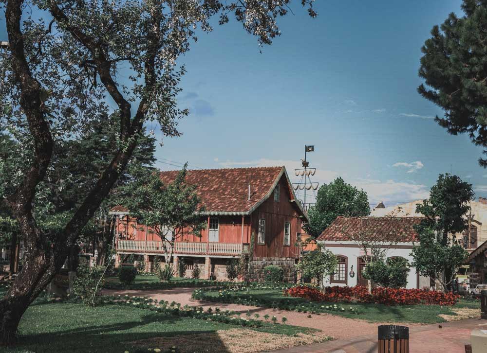 Casa laranja ao lado de casa branca em meio a árvores, durante o dia, em rua da cidade de Gramado, um dos lugares para viajar a dois