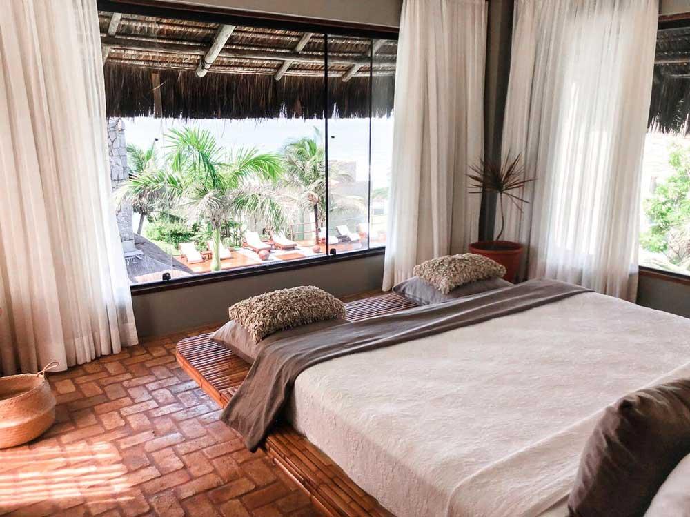 Cama de casal em quarto com cortinas abertas em Kilombo Villas & Spa uma opção de hospedagem para quem viajar para Praia da Pipa, um dos melhores lugares para viajar a dois