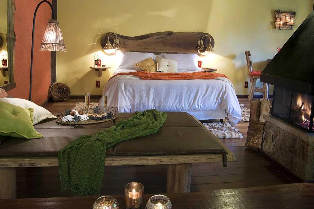 Quarto com cama de casal, abajur e lareira em Pousada dos Amores em Visconde de Mauá, um dos destinos mais românticos entre os melhores lugares para viajar a dois