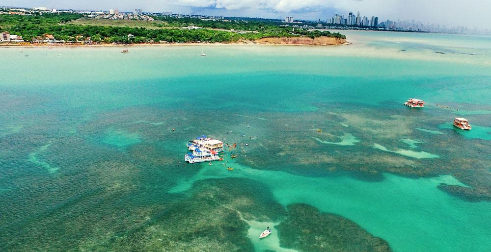 viajantes nadam perto de catamarãs em Piscinas Naturais do Seixas, uma das atrações entre muito o que fazer em João Pessoa